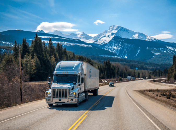 Semi-truck driving on highway with mountains in background