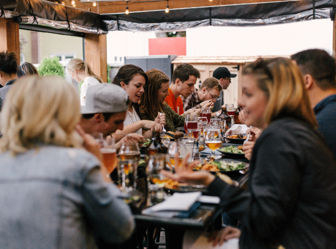 large group of people eating on outdoor patio in restaurant