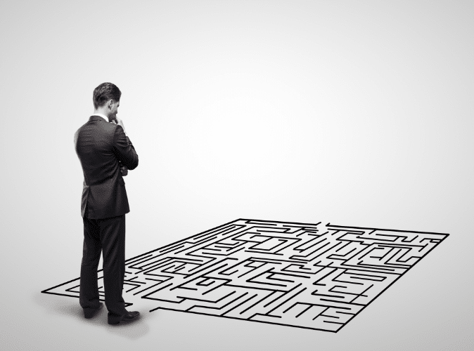businessman thinking and looking down at a puzzle