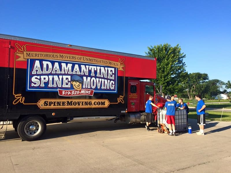 spine moving truck with movers in front
