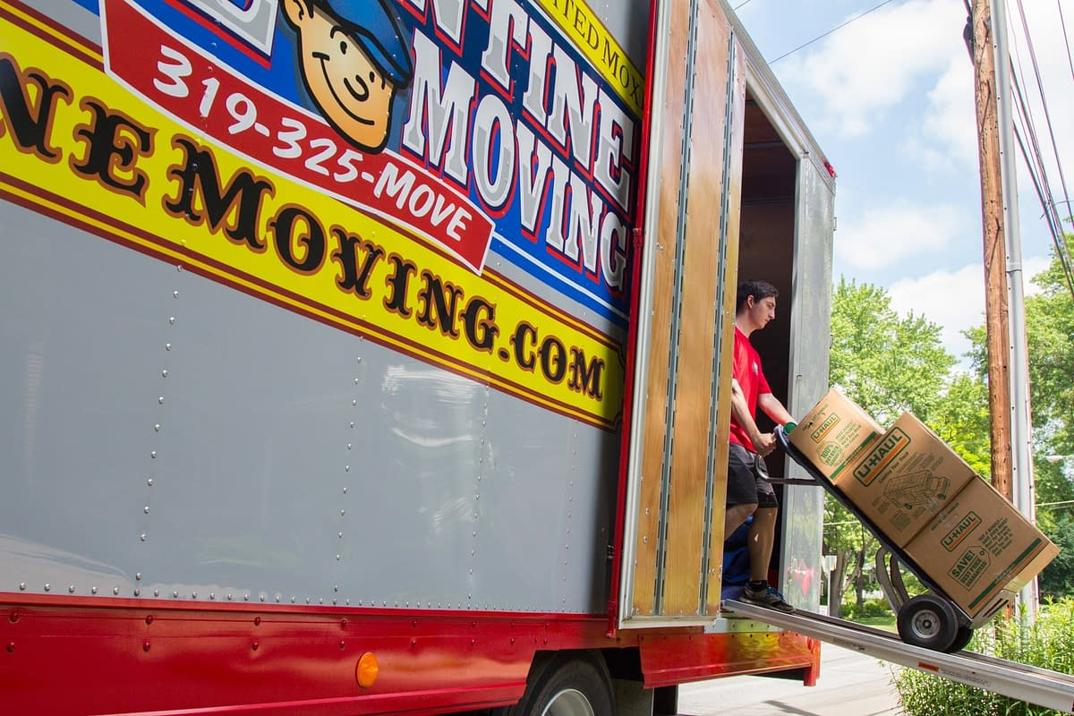 mover uses dolly to unload boxes from moving truck