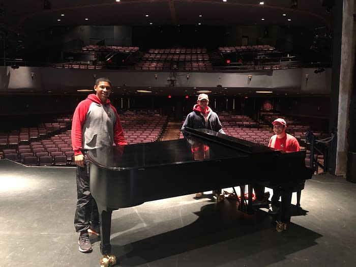 movers posing with a grand piano