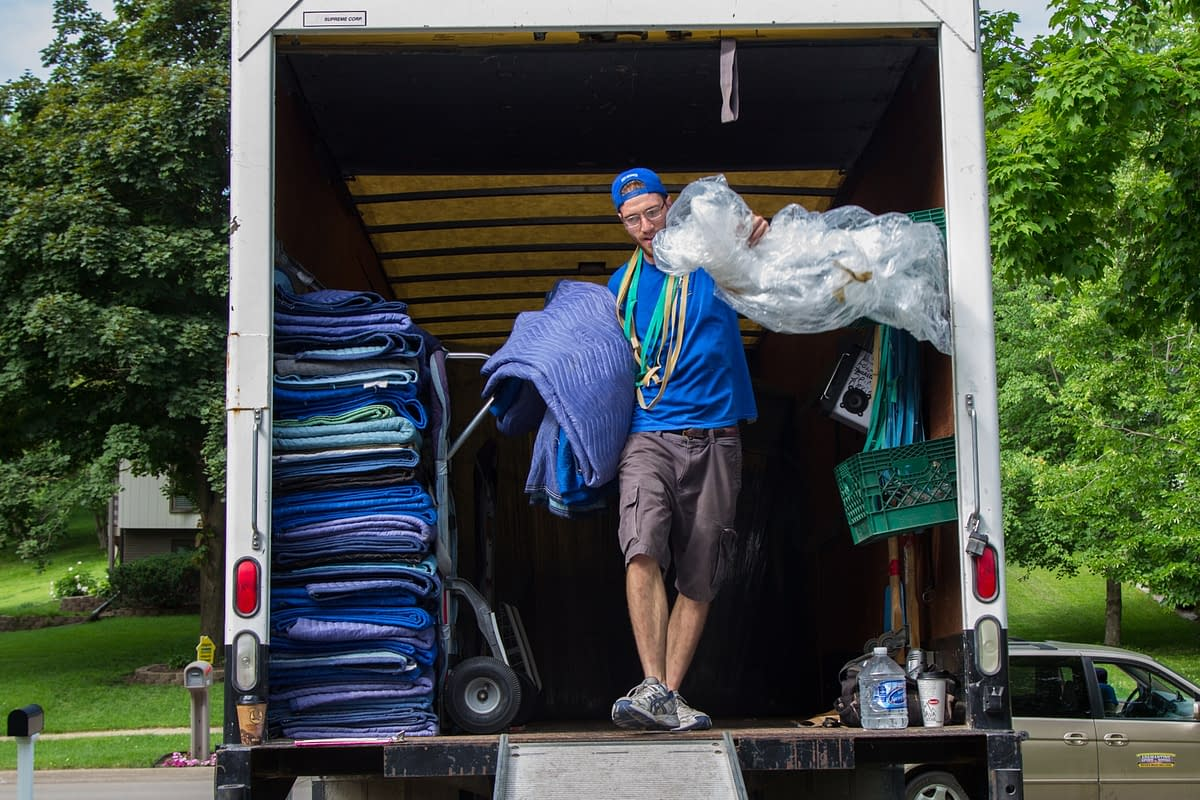 mover unloads blanketing from moving truck