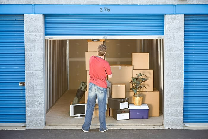 man closes storage unit containing boxes and other items