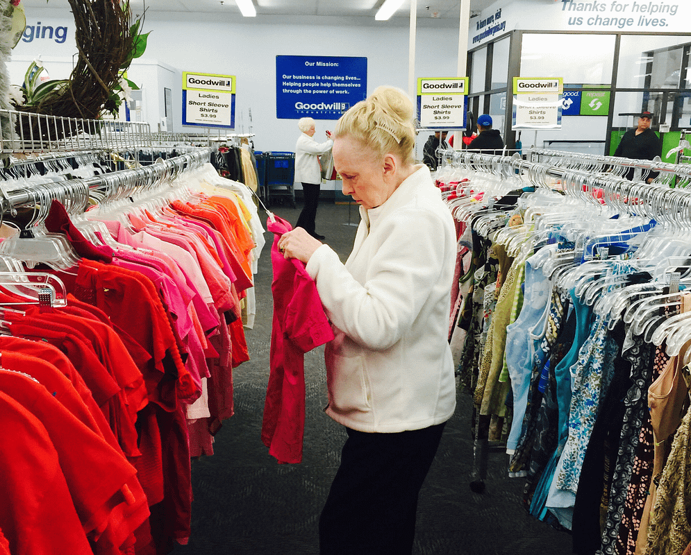 woman looking at shirt in Goodwill