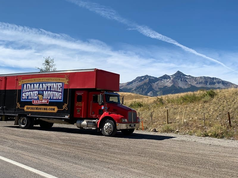 moving truck on highway with mountains in background