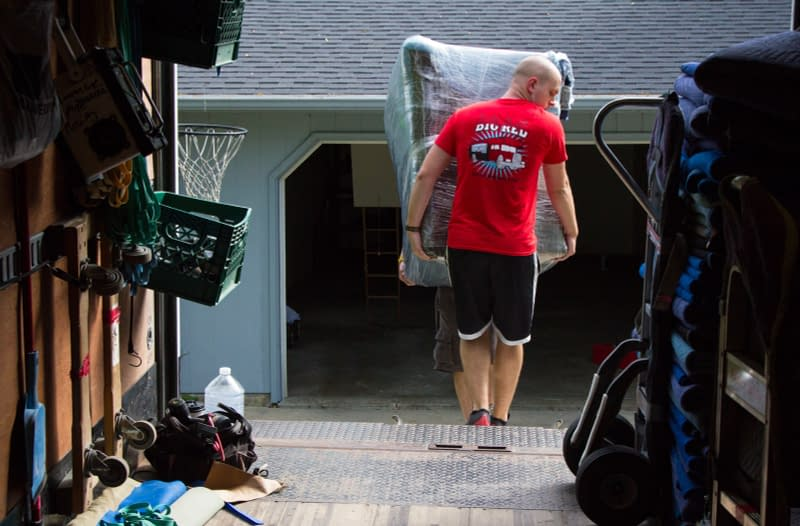 movers load a couch onto moving truck