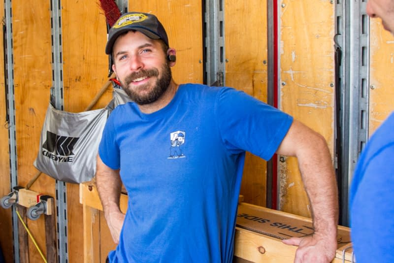 smiling man in blue shirt inside of moving truck