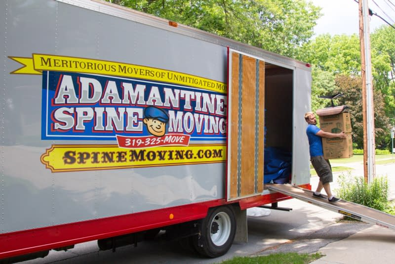 movers unload boxes from moving truck