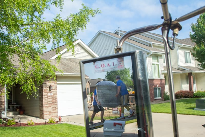 movers moving furniture viewed from rear view mirror