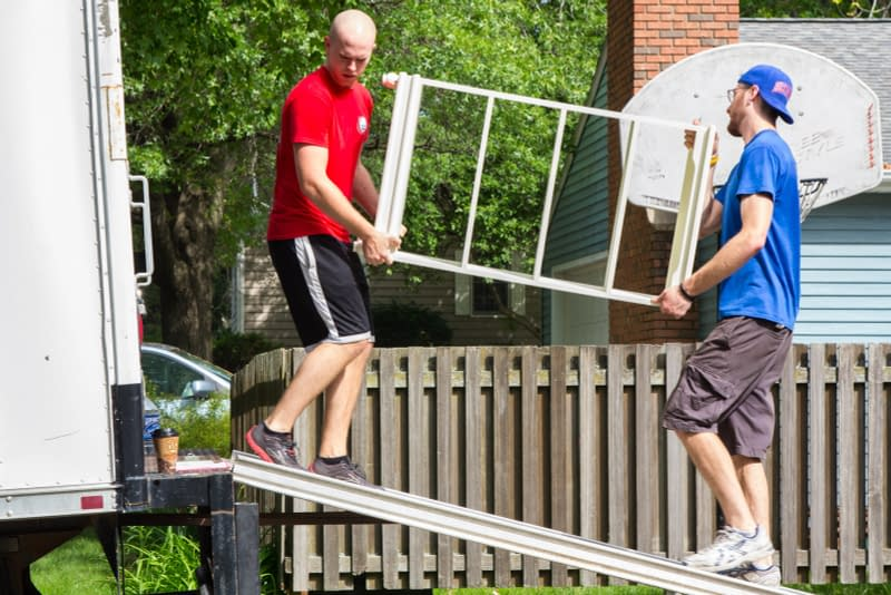 movers load furniture onto moving truck