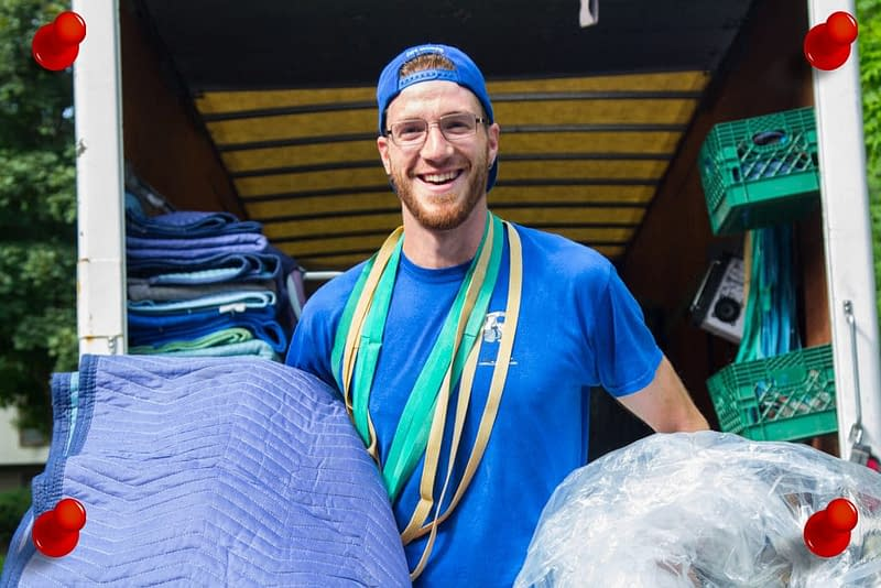 mover smiling and holding moving materials