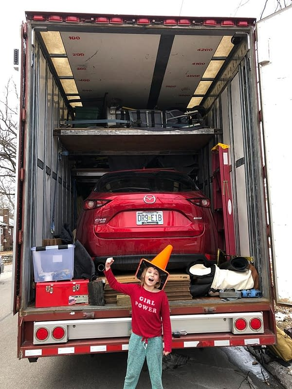 girl standing in front of moving truck with red car and other furniture inside
