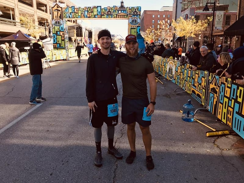 two runners smiling and posing for picture in front of race finish line