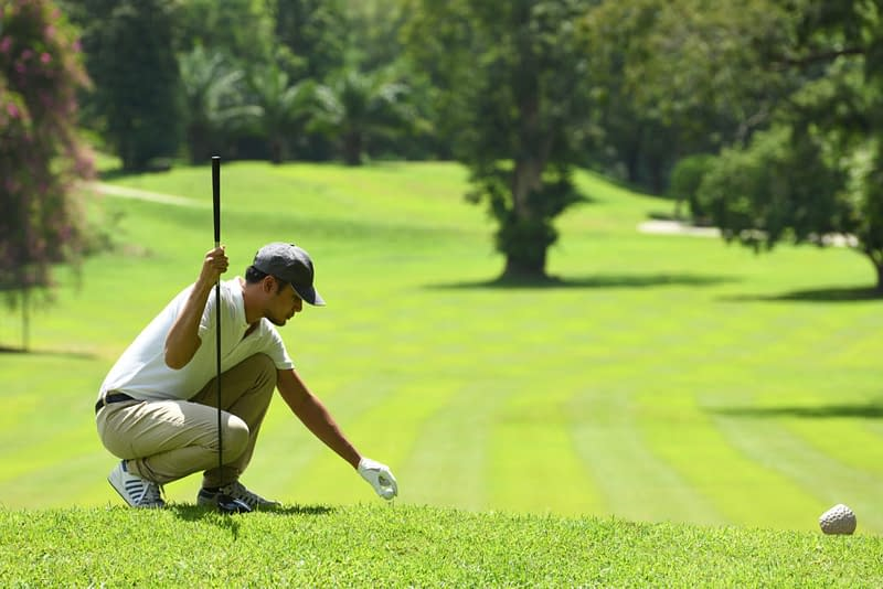 Young Man Playing Golf On A Beautiful Natural Golf Course
