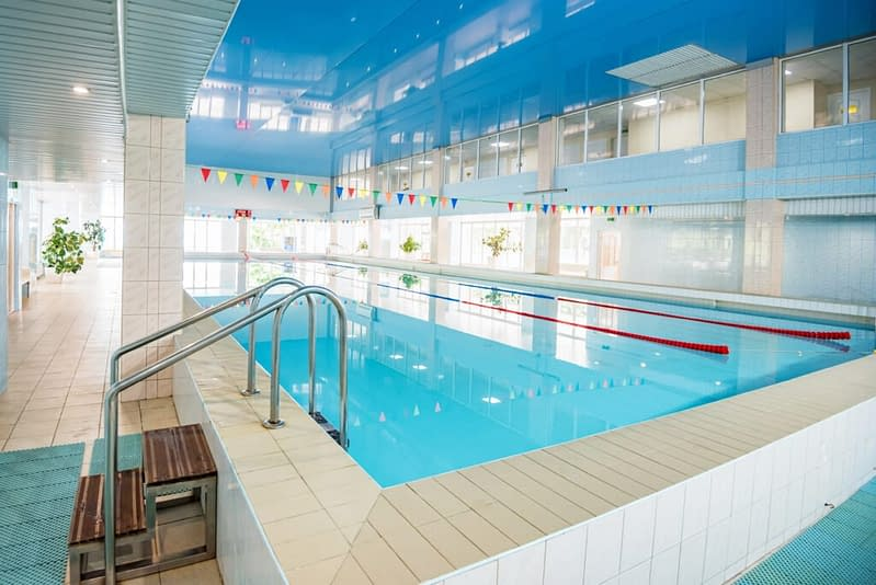 View Of Indoors Swimming Pool With Metal Ladder